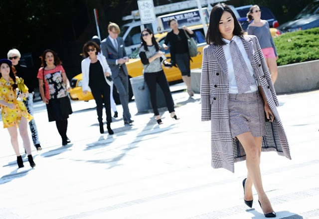 Street style photo of an Asian woman wearing a glen plaid coat and shorts
