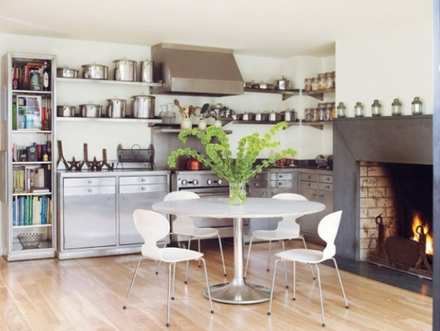 super small kitchen with stainless steel bottom cabinets and floating shelves, a circle table surrounded by white chairs and a fireplace