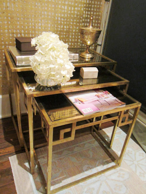 Three gold art-deco inspired nesting tables with a magazine, flower arrangement, wood box and a photo album in the Windsor house
