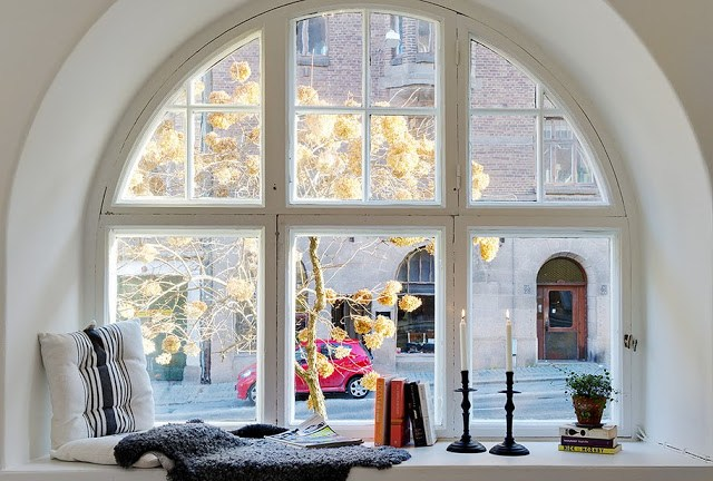 White cushion with black stripes, books a small potted plant and two candle sticks and a a throw on the ledge of an arched window