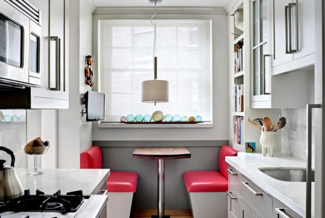 breakfast nook with red vinyl banquette bench seating and small galley kitchen with shaker cabinets, marble counter, and fisherman float balls in window