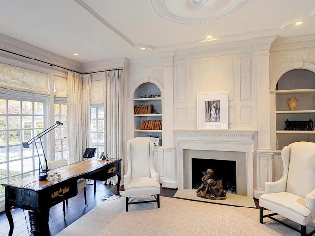 White study with writing desk, arched built in bookshelves shelves, a large window and dark wood floors