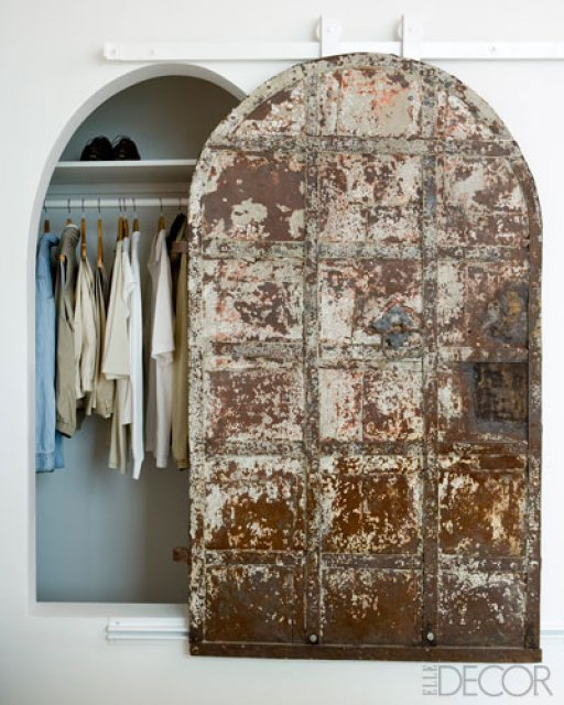 Antique arched French cellar door re-purposed as a closet door in a white modern Miami apartment.
