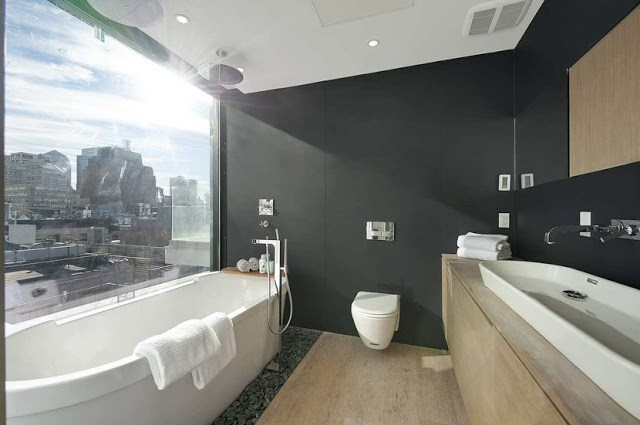 master bathroom with stand alone tub, custom vanity and black walls with an amazing view of the city