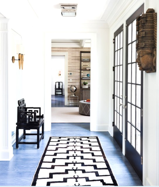 Hallway with blue stained wood floors, black paneled doors and a black chair with geometric arms