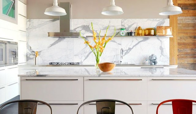 kitchen with white marble slab backsplash, an island, reclaimed wood and integrated stainless steel appliances and floating shelves