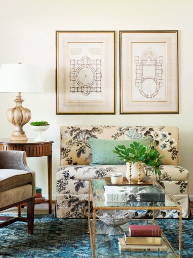 Living room with settee covered in the Schumacher Hollyhock chintz print, a glass coffee table and a blue patterned area rug