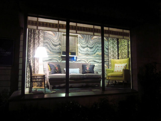 harbinger window display with wave wallpaper, velvet sofa, COCOCOzy quatrefoil curtains in gray reverse and a green armchair