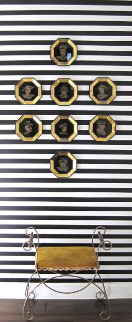 Hallway with black and white painted in horizontal stripes, 8 engraved portraits in gold octagon frames and an art deco metal stool with gold cushion