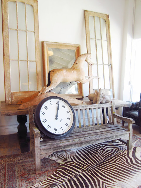 Brenda Antin store in Los Angeles with a reclaimed wood bench with a large clock sitting on it, zebra skin rug, a wood horse, windows