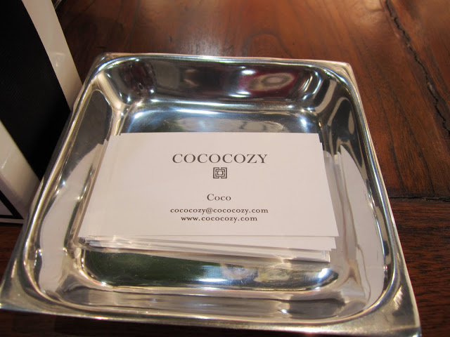 Coco's card in a silver dish on a wood table at the COCOCOZY booth during the New York International Gift Fair