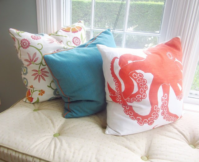 three decorative pillows on an upholstered cushion in a window seat