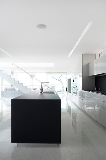 Modern white kitchen in the Flip Flop House with a black island