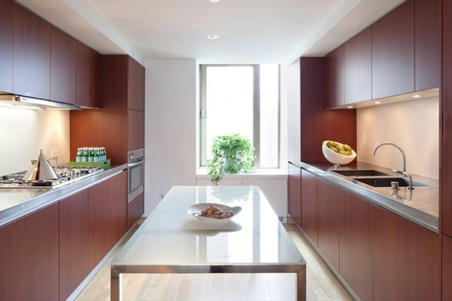 modern kitchen in a New York City penthouse with wood veneer cabinets and metal table island