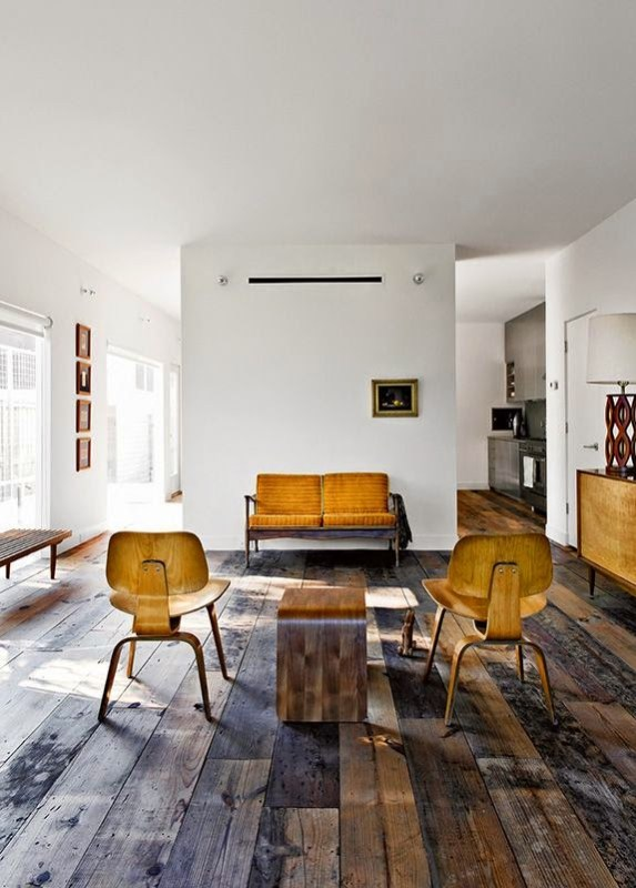 Modern living room with yellow chairs and rustic wood floor