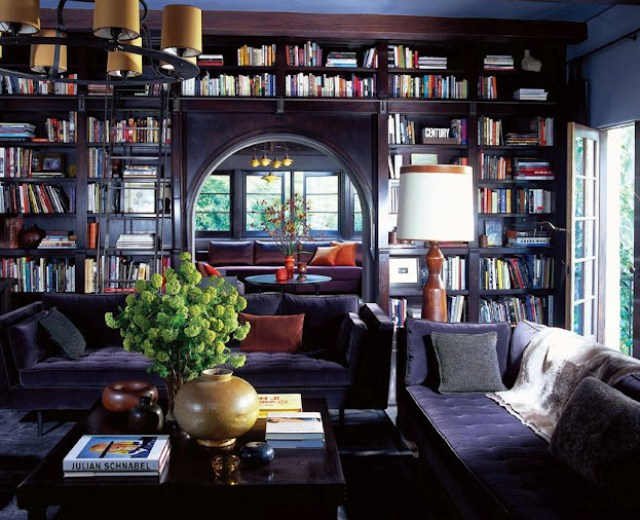 roman and williams' purple living room and den with built in bookshelves full of books bookcase, two purple sofas, a dark wood coffee table and round chandelier with yellow lampshades.