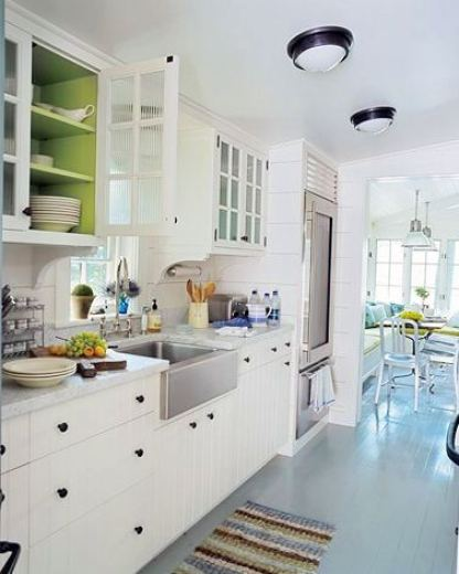Kitchen with white beadboard cabinet drawers, a stainless farmhouse sink, lime green upper cabinet interiors and a striped rug