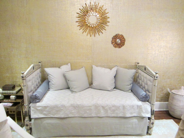 Upholstered day bed in the House of Windor's baby room with gold covering by Kneedler-Fauchere and two gold sunburst mirrors