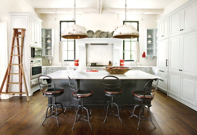 Kitchen with a large island that blends in with the dark wood floors, worn metal over sized pendant lights, white cabinets, and stainless appliances
