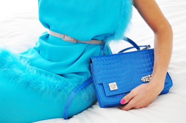 turquoise dress with feather trim, an electric blue crocodile bag and hot pink nails