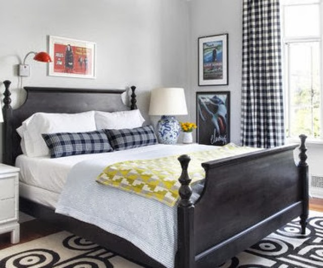 Bedroom with blue plaid pillows, black and white gingham curtains and a dark wood bed with white bedding