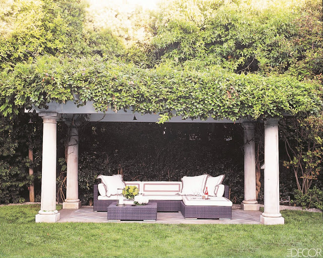 Backyard with an arbor made up of Doric columns and vines with an outdoor living room underneath