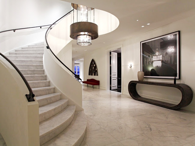 foyer with marble floors and staircase, and a chandelier light