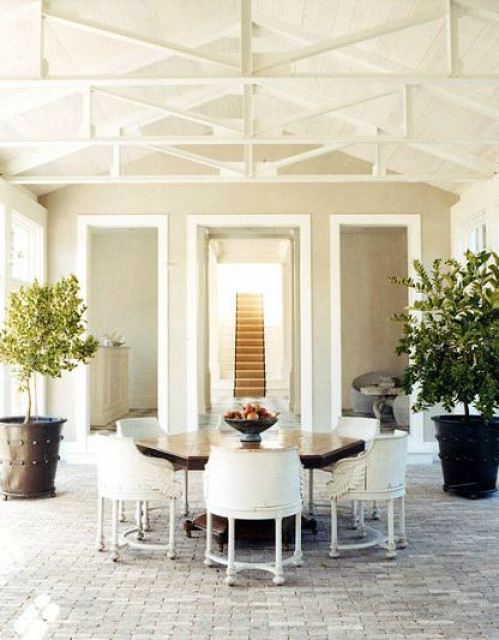 indoor dining room outdoor feel thanks to vaulted ceilings, visible beams, large metal plant pots holding small trees, octagon wood table, white wood chairs