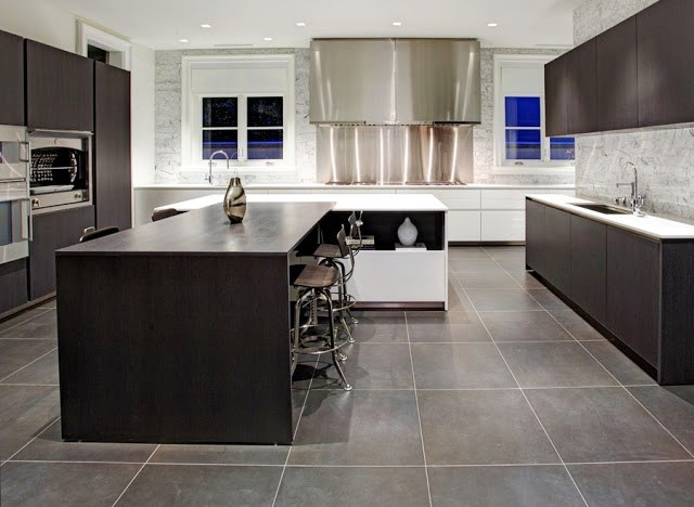 modern kitchen with large square slate tiling, sleek dark wood cabinets, a stainless steel hood and blacksplash cover