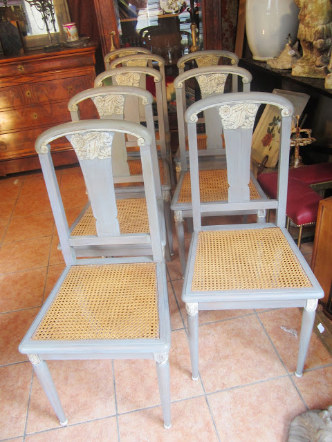 A set of 8 painted blue grey cane dining chairs with carved details on the legs