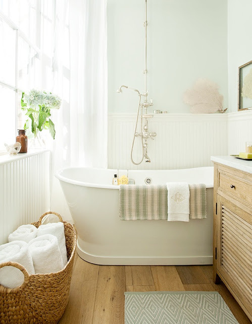 Bathroom with vintage cast iron tub, Perrin & Rowe fixtures and reclaimed white oak floors