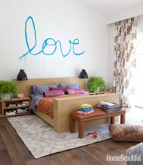 "Todd Nickey and Amy Kehoe of Nickey Kehoe's bedroom in their Malibu home featured in House Beautiful with ""love"" spray painted on the wall in cursive"