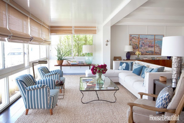 airy living room with white sofas, blue and white striped chairs and a glass table by Peter Dunham