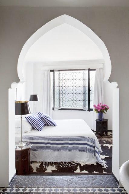 morrocan bedroom with doorway arch, tiles, iron on the window and an animal print rug