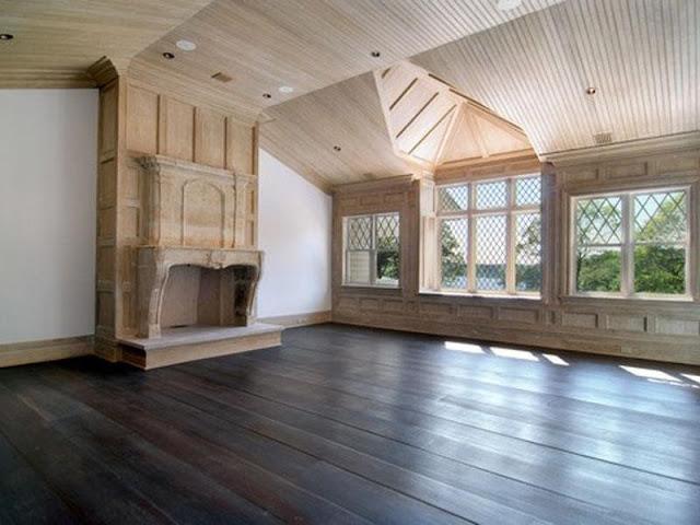 Unstaged bedroom Hamptons wood paneling windows fireplace