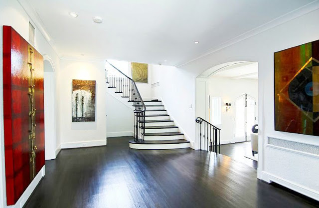 Grand foyer with dark wood floors, stairs with iron railings and large pieces of modern art
