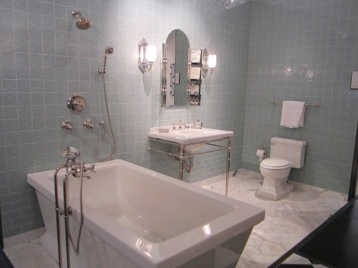 Alternative view of a bathroom with Michael S. Smith's Labyrinth tiles for Ann Sacks from floor to ceiling, an undermount sink where you can see the pipes. a marble tile floor and a freestanding tub