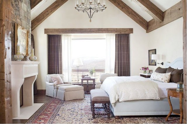 Caroline Edwards' bedroom in Aspen with rustic, pitch high ceilings, exposed beams, light blue upholstered bed, white molded fireplace
