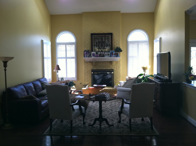 yellow family room with yellow painted brick fireplace, a sofa, two armchairs and a chest of drawers