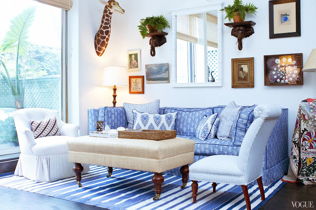 Blue and white living room in Rebecca de Ravenel's New York apartment with a blue and white sofa, white armchair, blue and white striped rug and an ottoman style coffee table