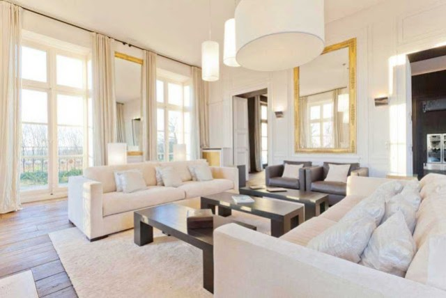 living room with white dueling sofas, french doors, three rectangular coffee tables, wood floors, pendant lights and a large mirror with a gold frame