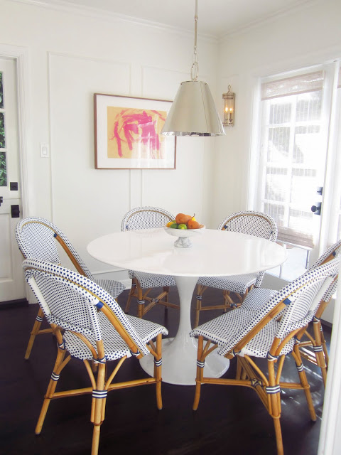 breakfast nook with saarinen tulip table, blue and white french cafe chairs, silver pendant light, and dark wood floors