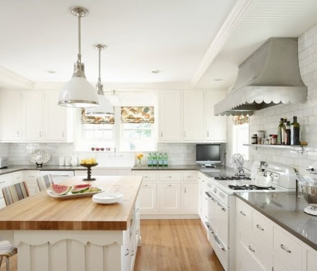 rehkamp larson architects' vintage kitchen roper stove with scalloped hood, butcher block island counter and pendant lights