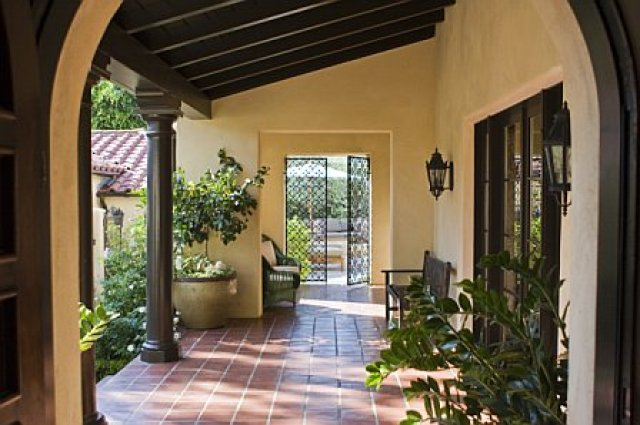 Los Angeles home after remodeling with a Spanish tiled covered walkway with columns, arches and beams leading from the front door to an ornate iron gate that opens onto a patio and pool area