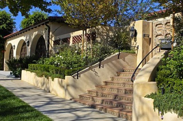 Exterior of a Cheviot Hills home after remodeling with stacked Spanish roof tile frill, arched garage doors and a carved wood gate entry door