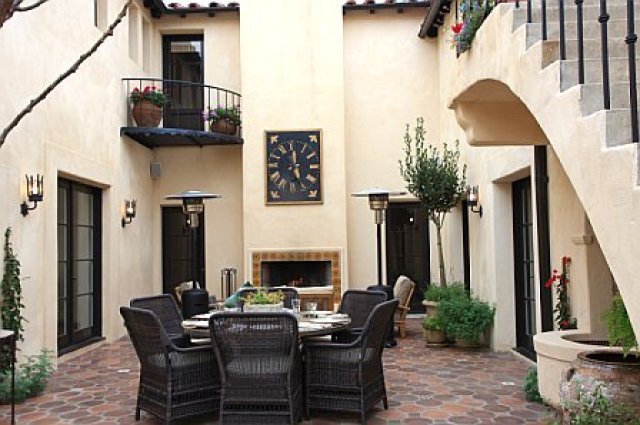 Kitchen courtyard is built out to include a tile patio and outdoor fireplace after remodeling