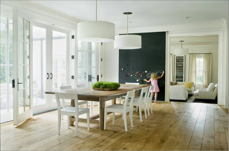 Simple dining room with large white drum pendant lights, a long wood farmhouse table surrounded by open back white chairs, wide plank wood floor, a wall of french doors and a floor to ceiling chalkboard