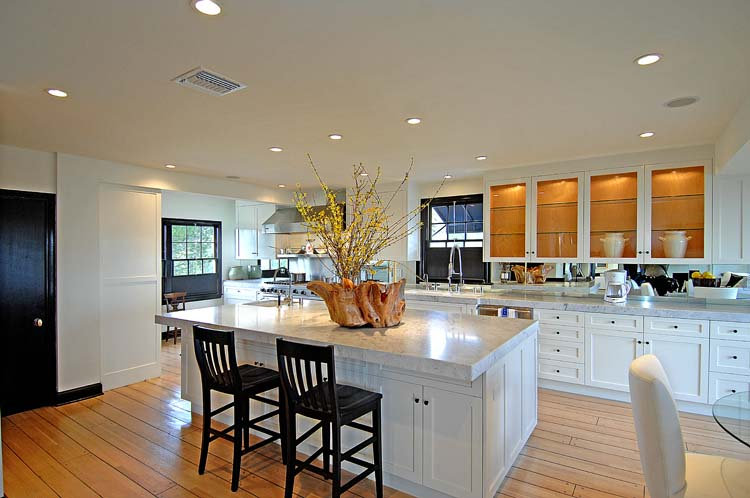 Long gourmet kitchen with a compact island with marble counter top, white upper cabinets with glass fronts and wide plank stained natural wood floors
