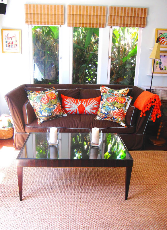 Brown sofa with turquoise piping and colorful accent pillows in a sea foam living room with striped orange roller shades