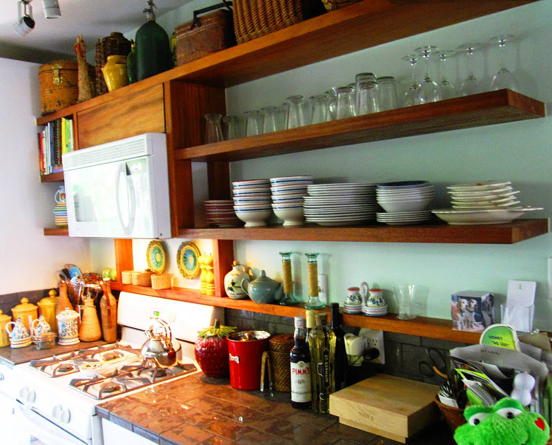 Gallery kitchen with open wood shelves holding antique finds and ceramic dishware